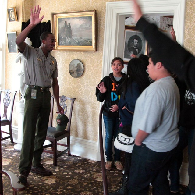 A ranger talks with a group of students in a historic parlor
