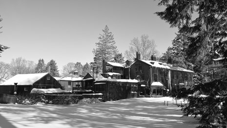 black and white image of historic house in snow