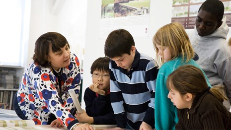 A landscape architect shows students a plan during a visit to her office