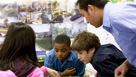 Students discuss a model of a park with a Landscape Architect