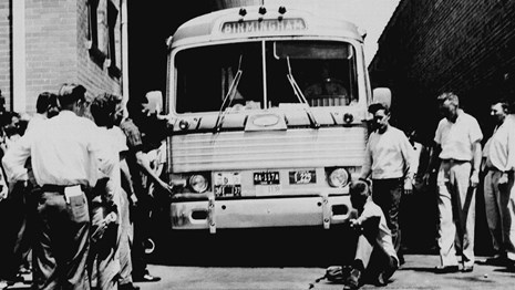 A white man sits in front of the Freedom Riders' bus, trying to prevent it from leaving the station