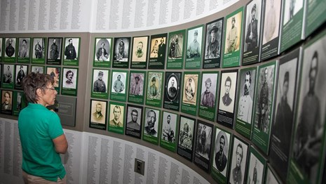Visitor examines wall of faces exhibit at the Chancellorsville Visitor Center