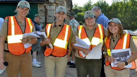 Four interns in tan polos and baseball caps wear reflective jackets while handing out fliers