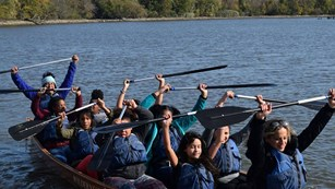 A group of students celebrate their canoe trip by raising their paddles up.