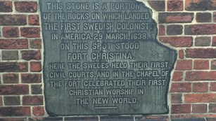 A photo of the original stone built into the fence that surrounds For Christina.