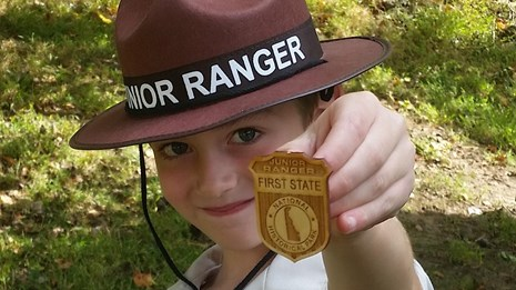 A boy wearing a Junior Ranger outfit shows off his new First State NHP Badge.