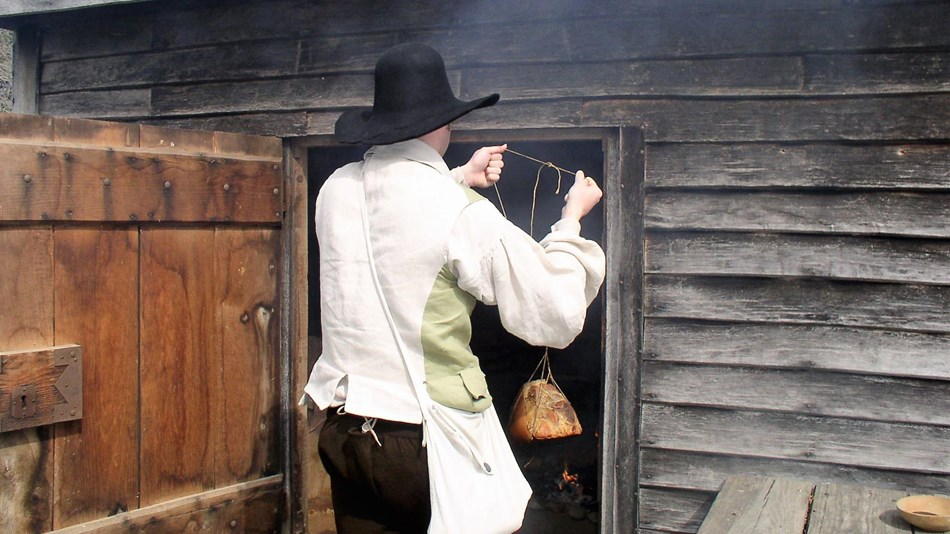 A gentleman is hanging meet in the smokehouse at the John Dickinson Plantation.