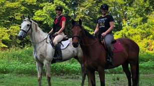 Two girls pose for a photo on horseback along the Brandywine Creek.