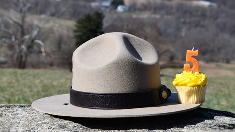 A cupcake with the number 5 sits on the edge of a ranger hat with rolling hills in the background.