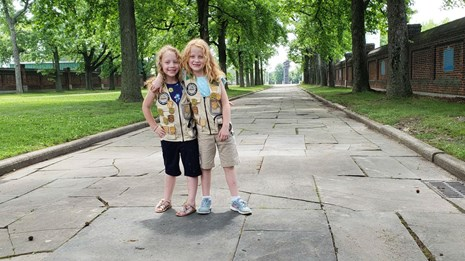 Two kids pose at Fort Christina with their Junior Ranger Badge.