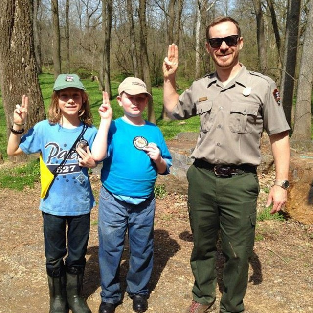 Park Superintendent poses with a Girl Scout and a Boy Scout.