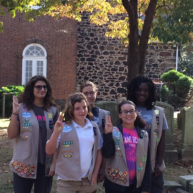 Five Girl Scouts pose in front of Old Swedes Church next to a few gravestones.
