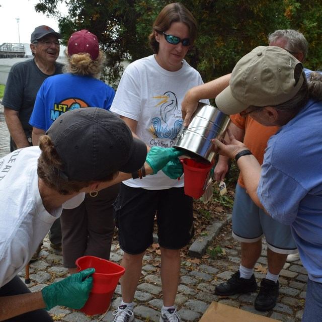 Volunteers pour paint into a small container.