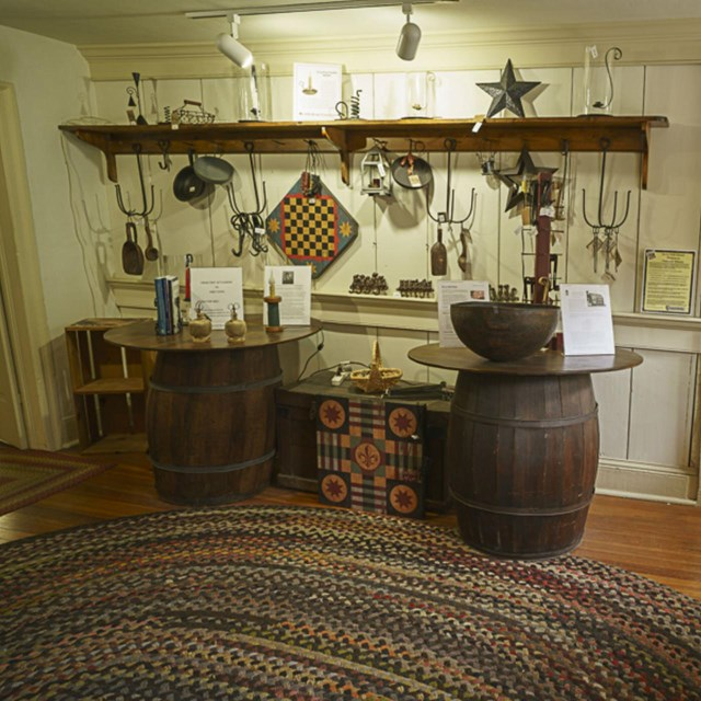 Two whiskey barrels make a table with knickknacks hanging on the wall inside the house.
