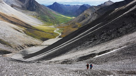 Hikers ascending a rocky slope in the mountains