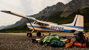 A bushplane drops off a load of gear and people on a river bar in the mountains