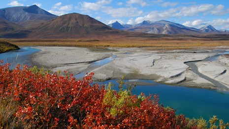 Distant mountains rise high while the Noatak River flows past fall colors in the foreground