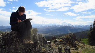 woman sitting on a rock, making notes on a clipboard