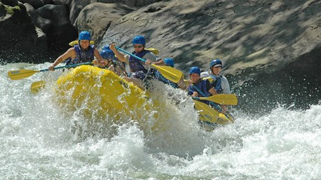 whitewater rafters crash through a rapid