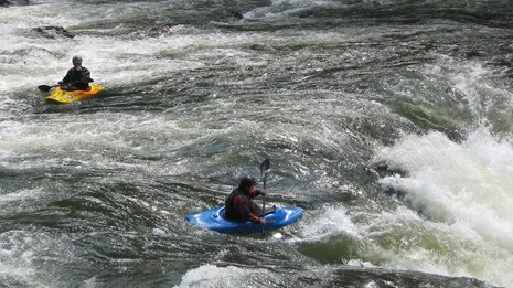 two kayakers approach rapids