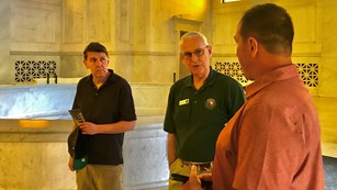 A Volunteer-In-Parks talks with two visitors inside the Mausoleum