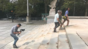 A videographer films a three people walking up the stairs of the Mausoleum