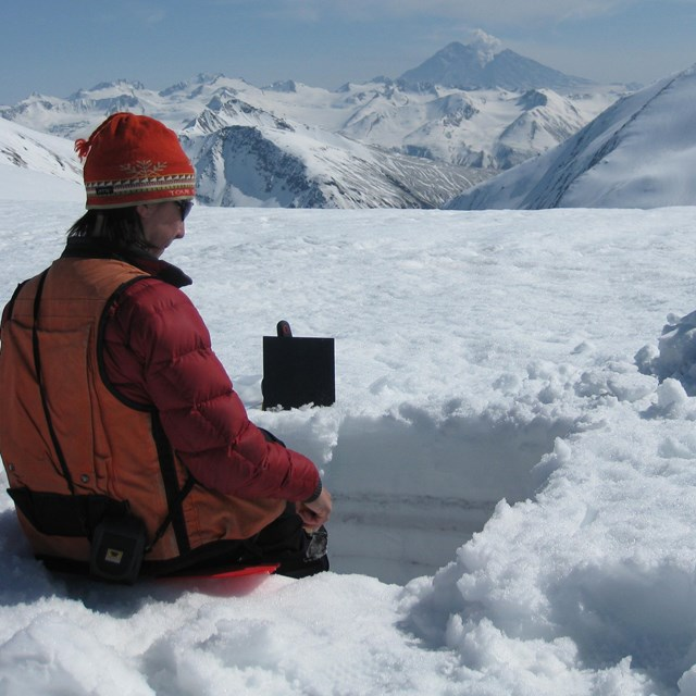 person in snow survey pit