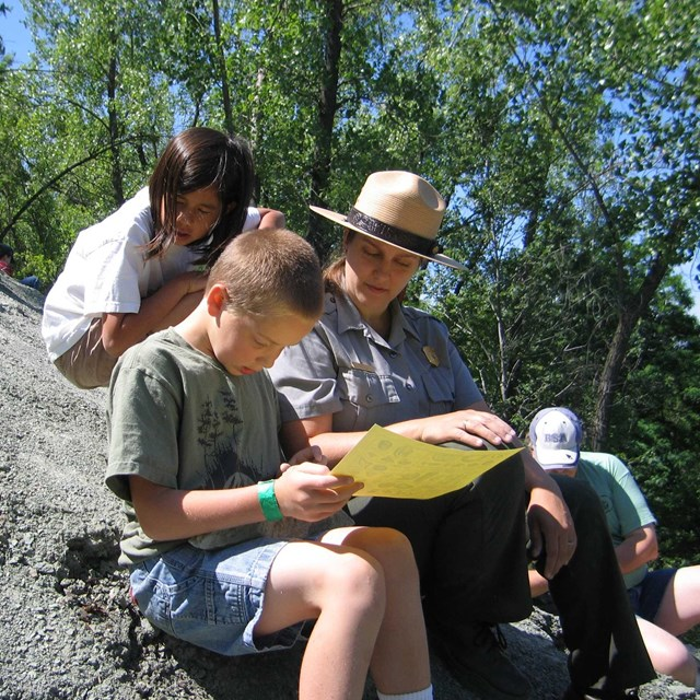 ranger with children at a fossil site