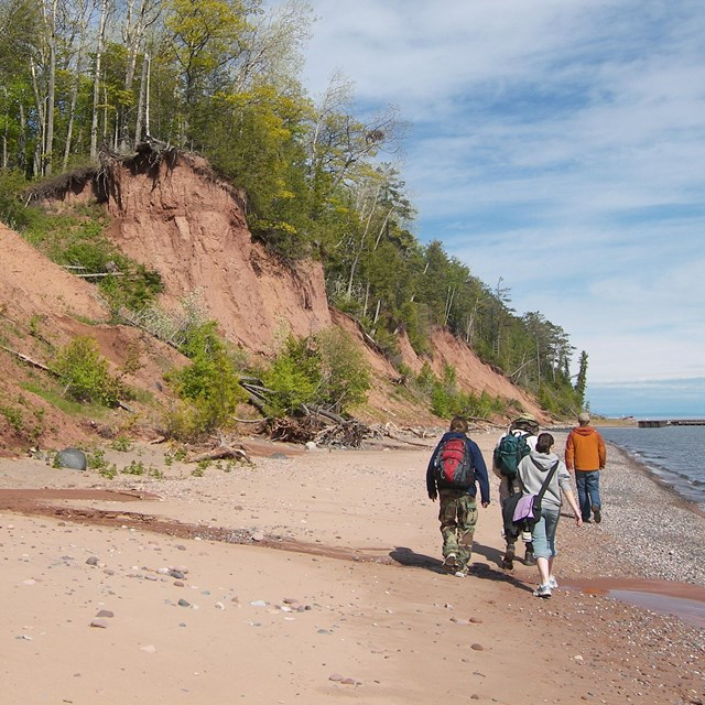 red-hued shoreline bluffs and sand beach