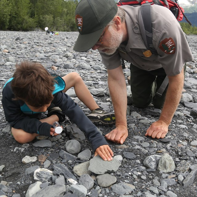ranger and youth examining rocks in gravel bar