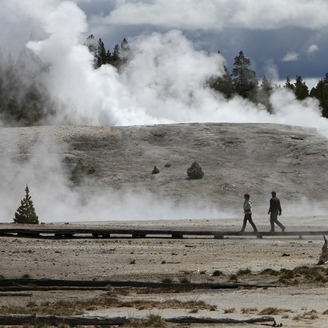 two people walking in area with steam rising from the ground