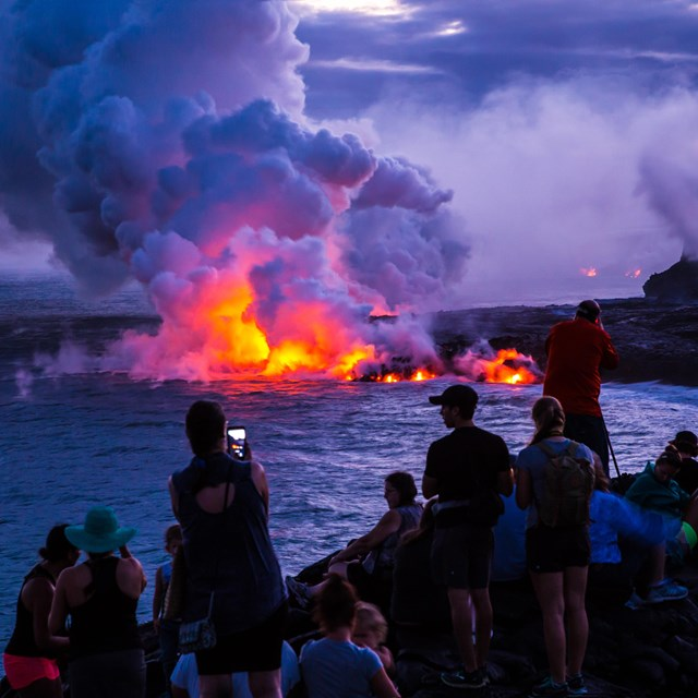 evening scene of molten lava entering the ocean, steam rising, people watching