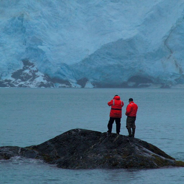 scientists on tiny island with massive tidewater glacier in background