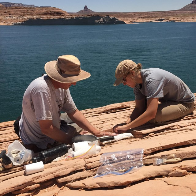 two people working on a fossil site near lake