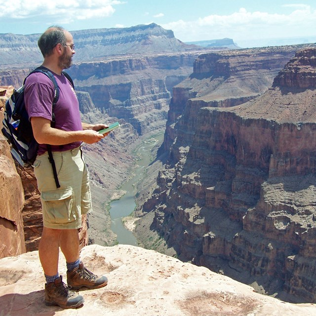 person standing on the rim of the Grand Canyon