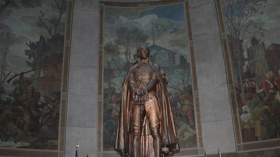 Clark statue and 3 murals behind him