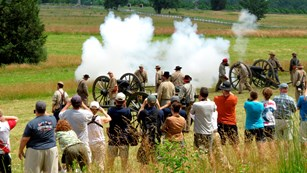 Confederate living historians demonstrate how to load and fire a cannon to a large group of visitors