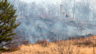 A prescribed fire moves across the western face of Little Round Top from left to right through field