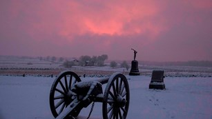 Snow covers the battlefield, a cannon and two monuments are in the center and pink and purple clouds