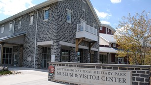 The park sign is visible in front of the corner of the Museum and Visitor Center.