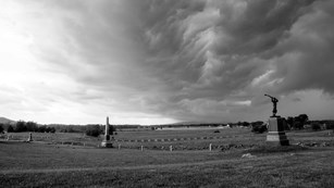 A black and white photo of storm clouds over the battlefield, two monuments are in the foreground.