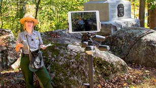 A park ranger stands beside a monument as she presents a virtual program via a digital tablet.