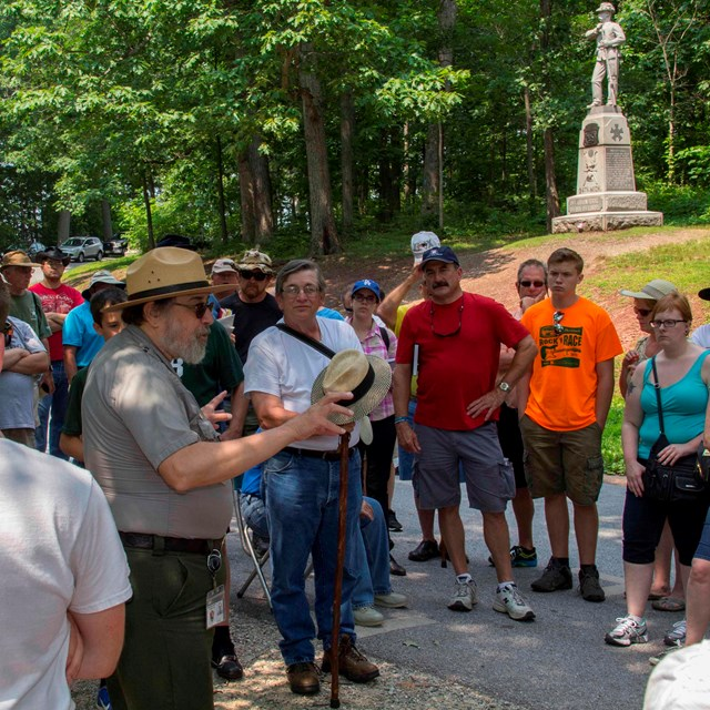 A park ranger presents a program on the battlefield. He is surrounded by dozens of visitors.