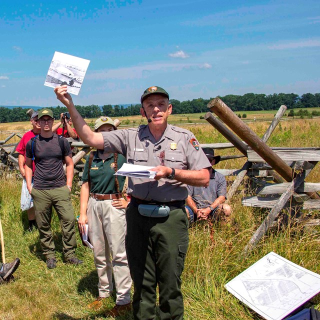 A park ranger shows the crowd a picture during a battle walk in an open field with a wooden fence.