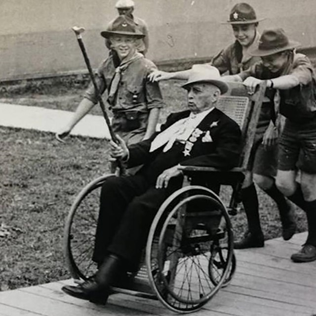 A group of boy scouts help push a veteran of the Battle of Gettysburg around in his wheel chair.