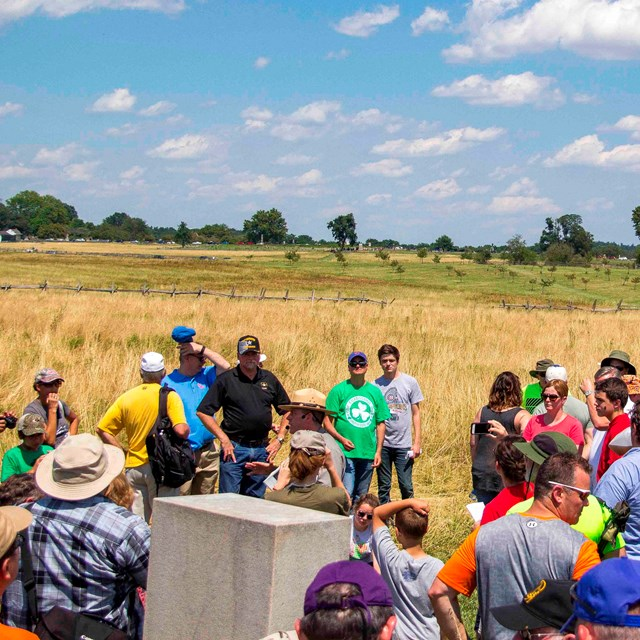 A park ranger leads a Pickett's Charge battle anniversary program to a large crowd in an open field.
