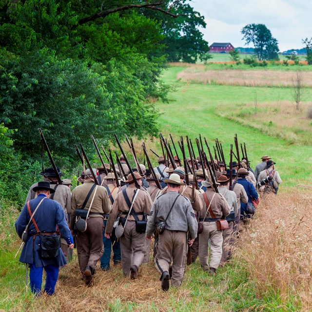 A group of Confederate living historians march across the field. A red barn is in the distance.