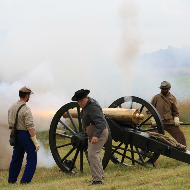 A group of Confederate artillery living historians fire a cannon during a demonstration.