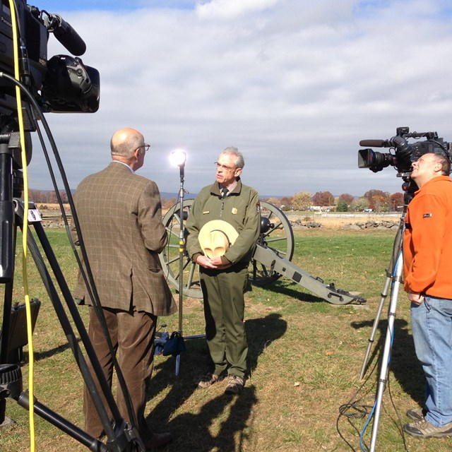 A park ranger stands on the battlefield conducting an interview with the media.