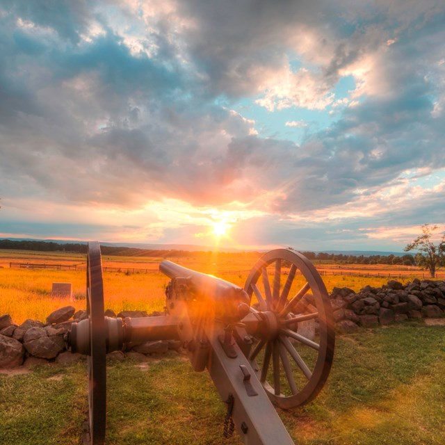 The sun is setting over the battlefield. Two cannons are in the foreground along a stone wall.